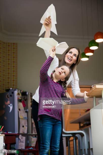 happy mother and daughter throwing paper plane together at home - lanzar actividad física fotografías e imágenes de stock