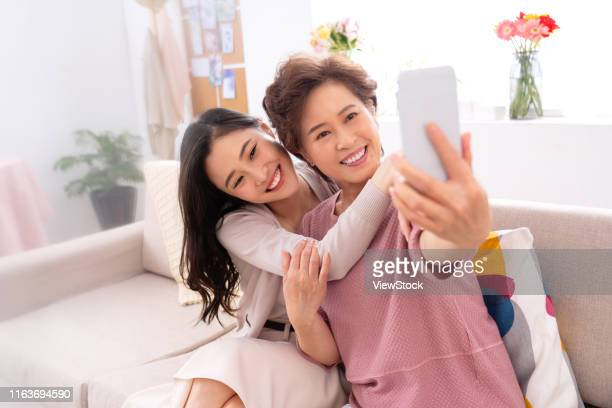 happy mother and daughter to use mobile phones - chinese mothers day stock pictures, royalty-free photos & images