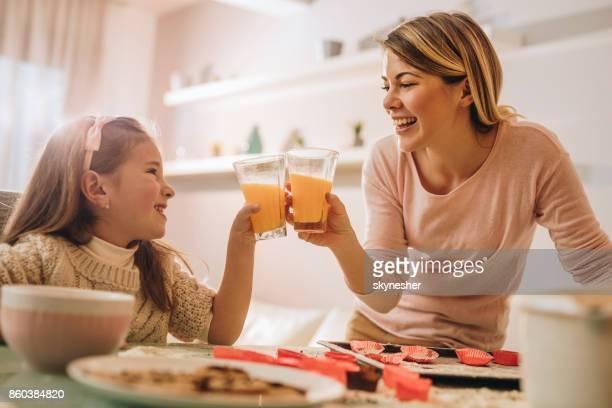 feliz mãe e filha brindando com suco enquanto cozinhava. - fazer um bolo - fotografias e filmes do acervo