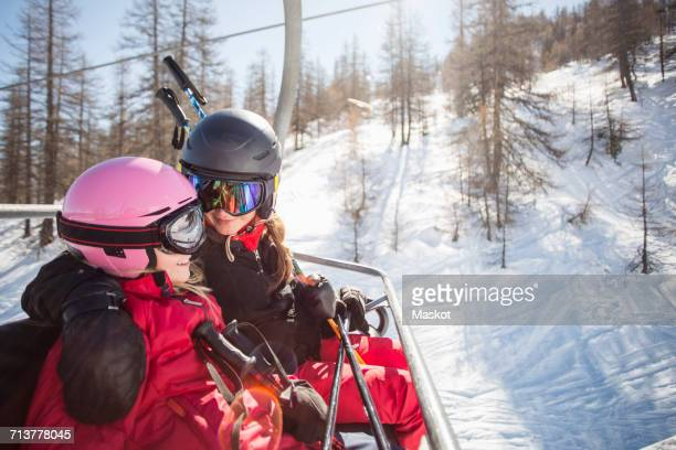 Happy mother and daughter traveling in ski lift