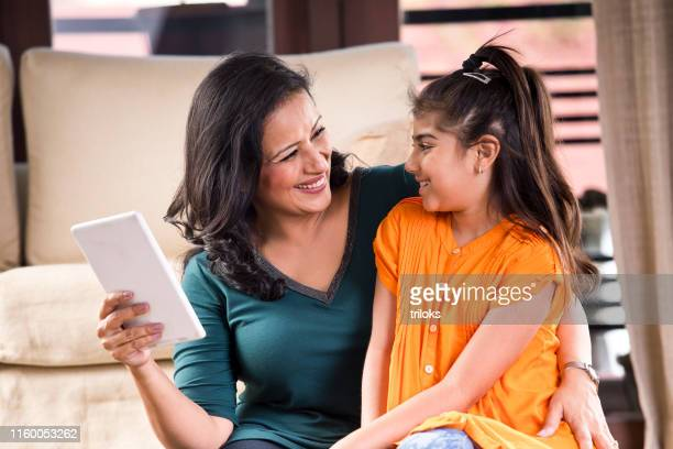 happy mother and daughter using digital tablet - one parent stock pictures, royalty-free photos & images