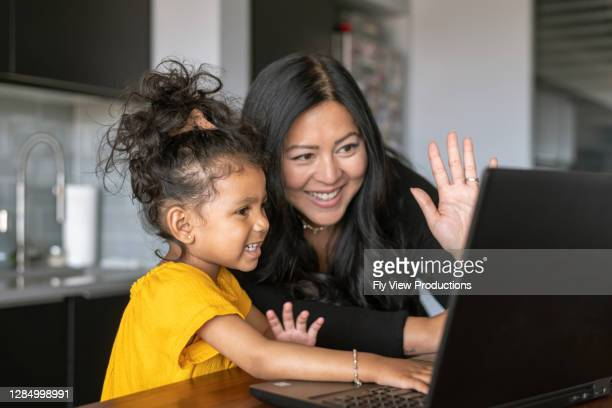 happy mother and daughter using video chat on laptop computer to talk to family and friends - innocence stock pictures, royalty-free photos & images