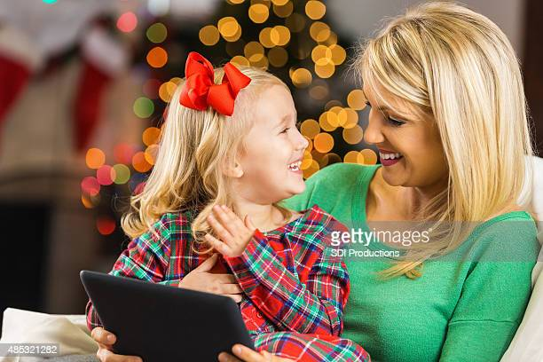 Happy mother and daughter video chatting with family on Christmas