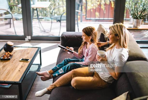 happy mother and daughter watching tv at home. - watching tv stock pictures, royalty-free photos & images