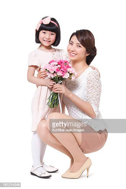 Happy mother and daughter with a bouquet of carnation