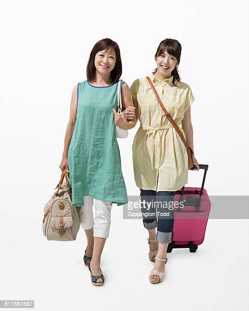 Happy Mother And Daughter With A Suitcase And Bag