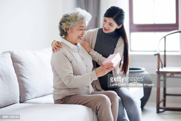 happy mother and daughter with gift box - chinese mothers day stock pictures, royalty-free photos & images