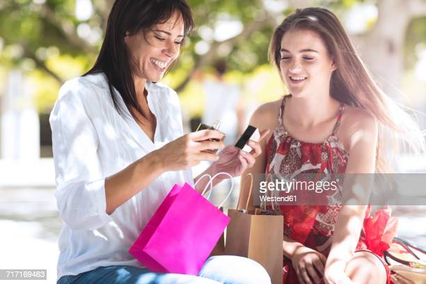 happy mother and daughter with shopping bags in the city - gift lounge stock-fotos und bilder
