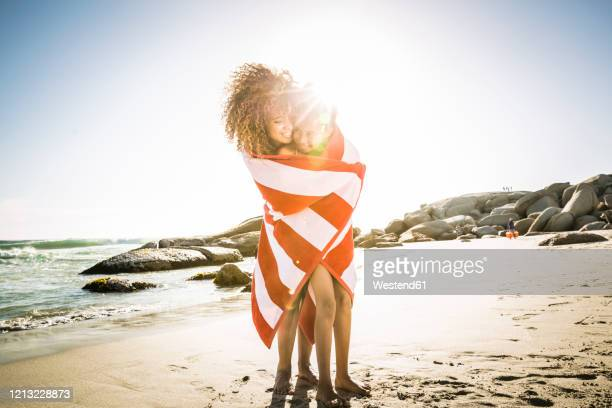 happy mother and daughter wrapped in a towel on the beach - wrapped in a towel stock pictures, royalty-free photos & images