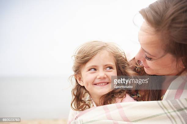 happy mother and daughter wrapped in blanket - hot mom stock photos and pictures