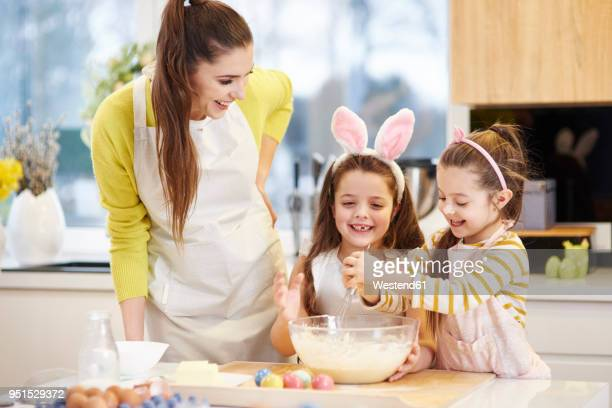 happy mother and daughters baking easter cookies in kitchen together - happy easter mom ストックフォトと画像