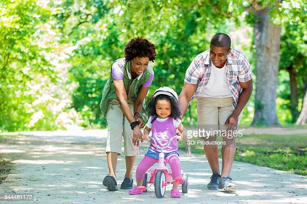Happy Mother and Father teaching toddler daughter to ride tricycle