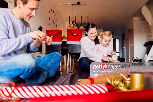 Happy mother and father with daughter wrapping Christmas presents at home