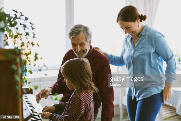 Happy mother and great grandfather looking at boy playing piano in house