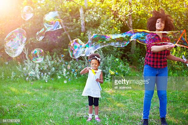Happy mother and her daughter playing soap bubbles in park.