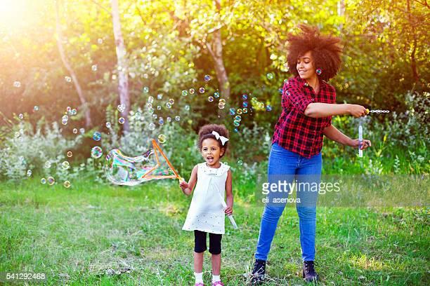 Heureuse Mère et sa fille jouent bulles de savon dans le parc.