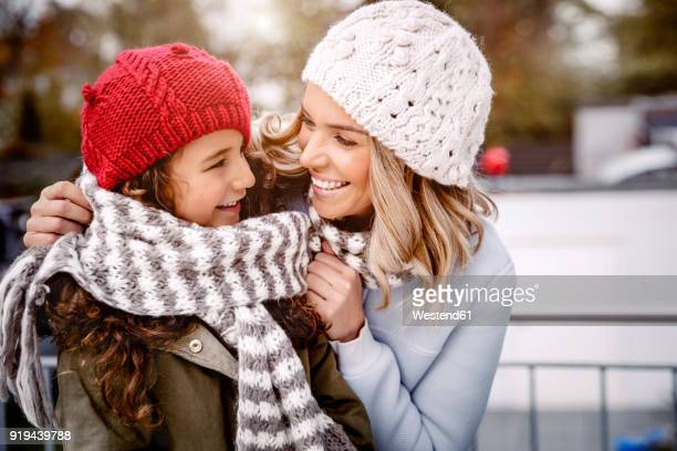 happy mother and her little daughter wearing woolly hats and knitted scarf - kopfbedeckung stock-fotos und bilder