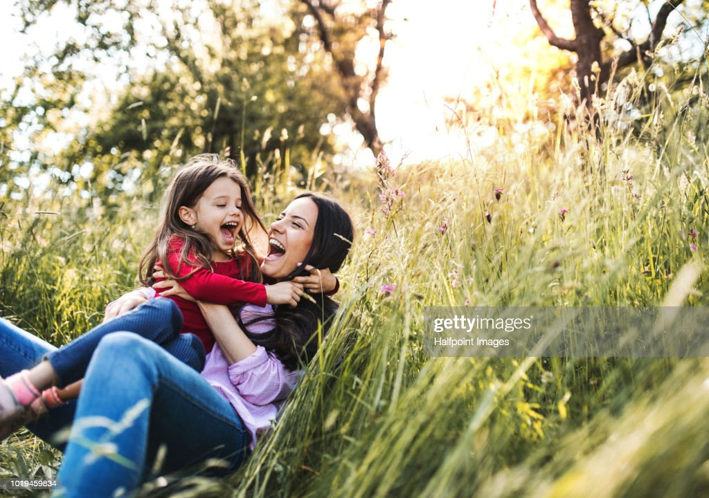 Happy mother and her small daughter lying down on the grass in spring nature, laughing. : Stock-Foto