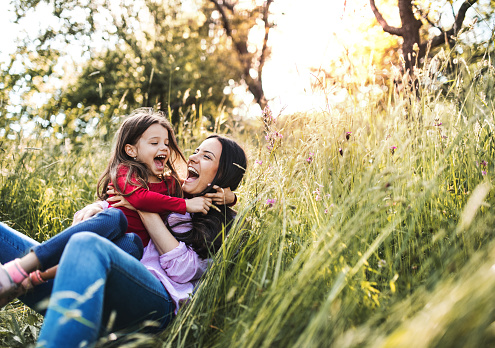 Happy mother and her small daughter lying down on the grass in spring nature, laughing. - gettyimageskorea
