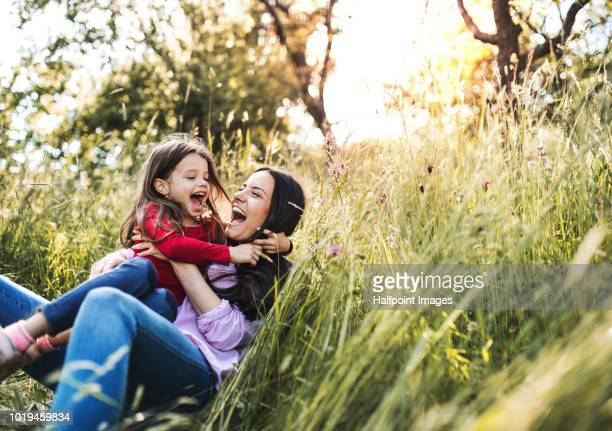 Happy mother and her small daughter lying down on the grass in spring nature, laughing.