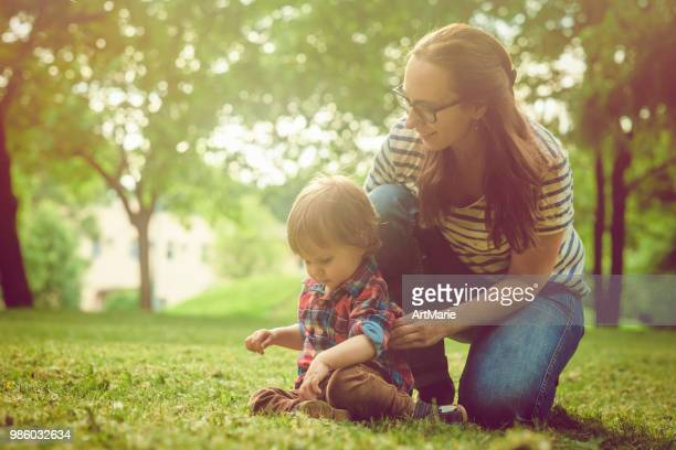 Happy mother and her son enjoying summer in park