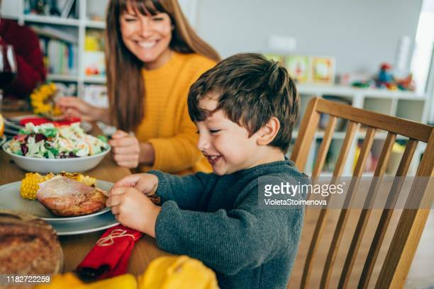 happy mother and her son having fun while eating turkey leg - kids thanksgiving stock pictures, royalty-free photos & images