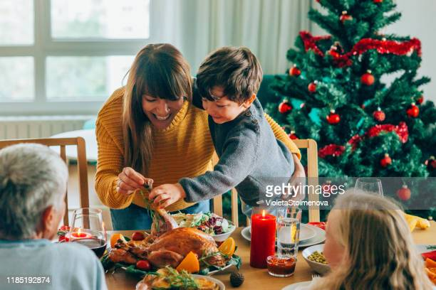 happy mother and her son having fun while holding roasted turkey leg - evening meal stock pictures, royalty-free photos & images