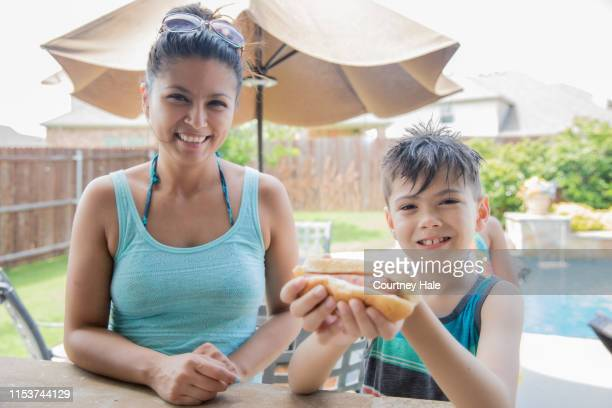 happy mother and her young son eating hot dogs at neighborhood party - filipino family dinner stock pictures, royalty-free photos & images