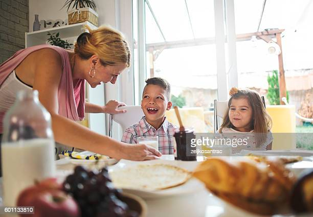 happy mother and kids having breakfast in kitchen