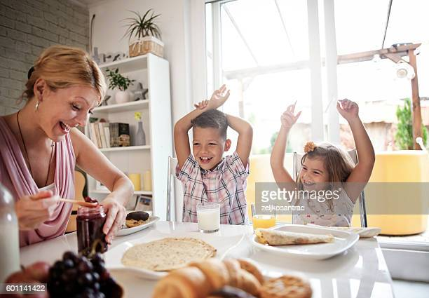 happy mother and kids having breakfast in kitchen