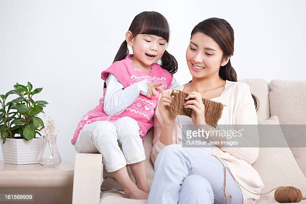 Happy mother and little daughter knitting at home