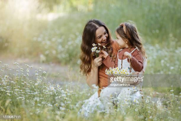 glückliche mutter und kleines mädchen, das blumen pflücken - muttertag blumen stock-fotos und bilder