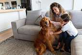 Happy mother and son at home petting their dog