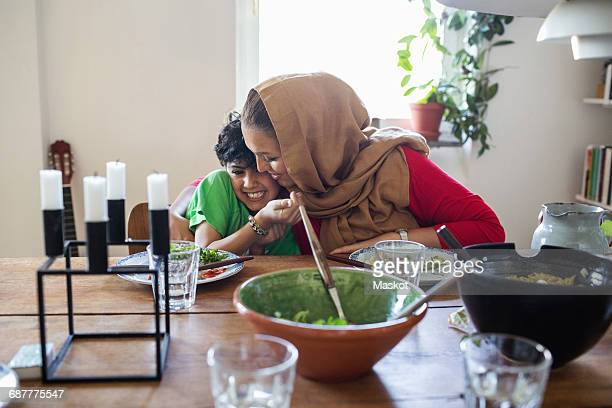 Happy mother and son embracing at dining table