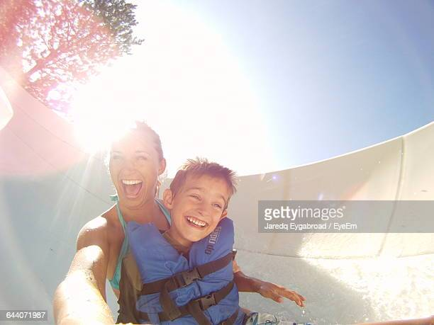 Happy Mother And Son Enjoying Water Slide During Sunny Day