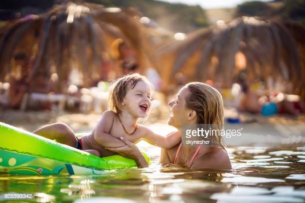 Feliz mãe e filho se divertindo no mar durante o dia de verão.