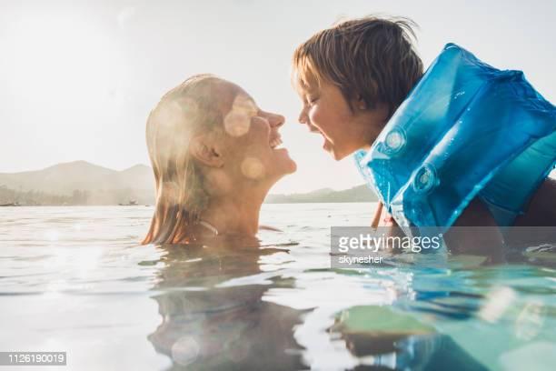 feliz mãe e filho se divertindo enquanto nadava no mar, nas férias de verão. - família de um filho - fotografias e filmes do acervo
