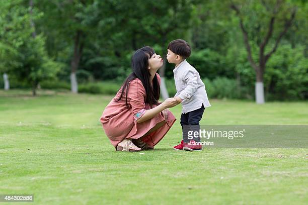 happy mother and son on the green grass