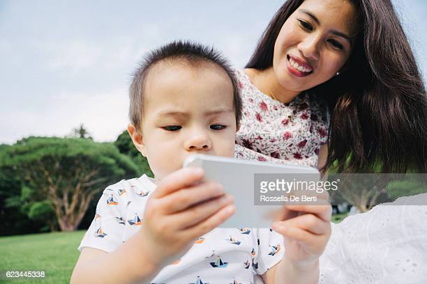 Happy mother and son outdoors surfing the net on smartphone