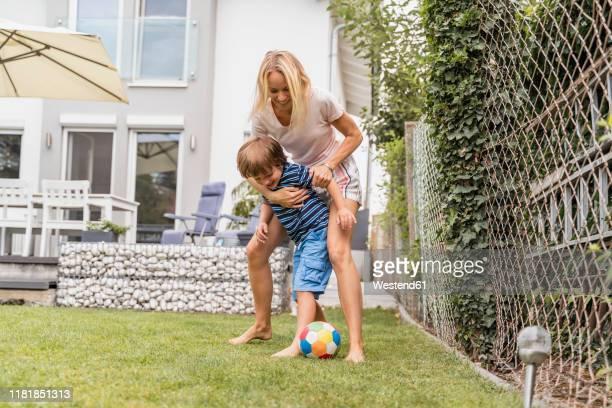happy mother and son playing football in garden - mama futbol fotografías e imágenes de stock