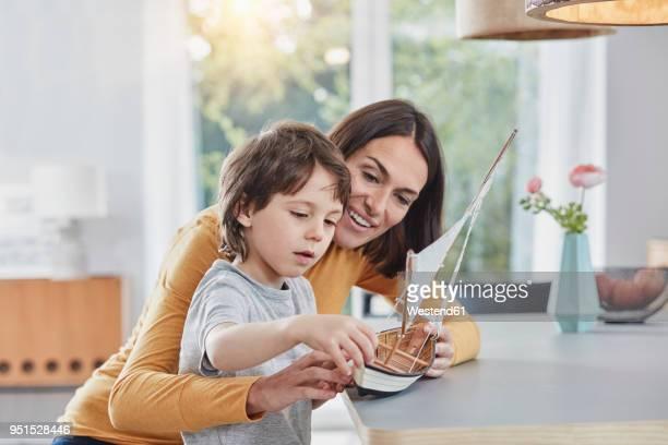 happy mother and son playing with model boat at home - mamma e figlio foto e immagini stock