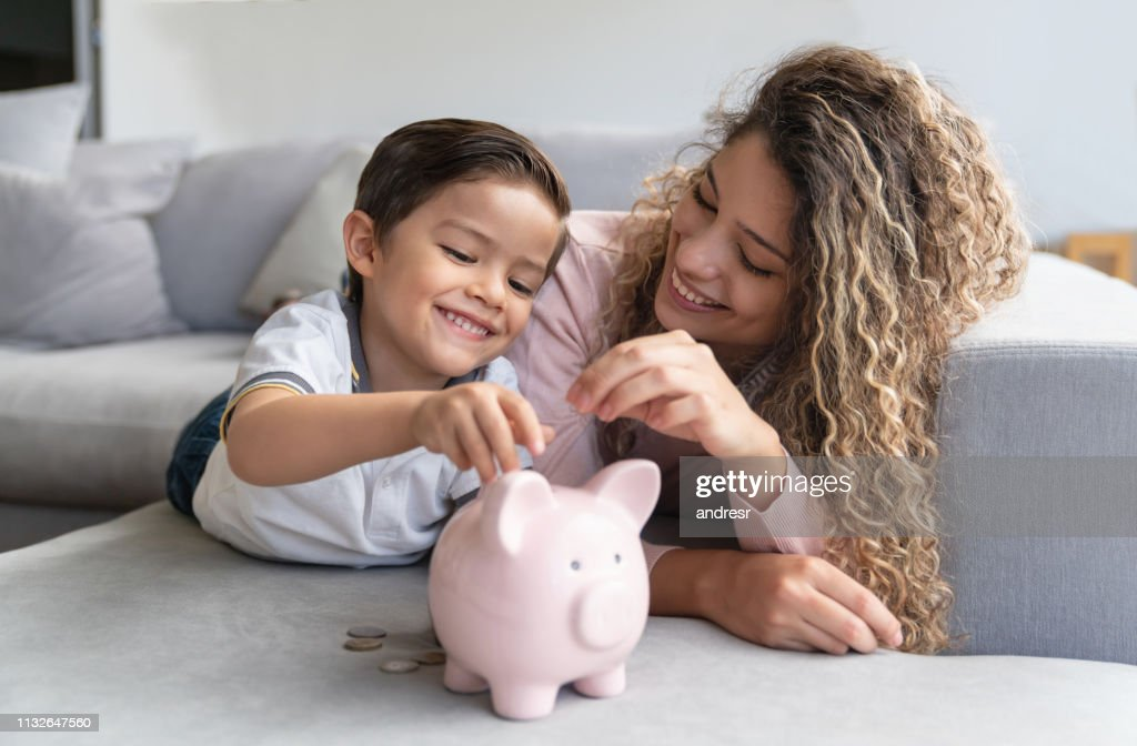 Glückliche Mutter und Sohn sparen Geld in einem Sparschwein : Stock-Foto