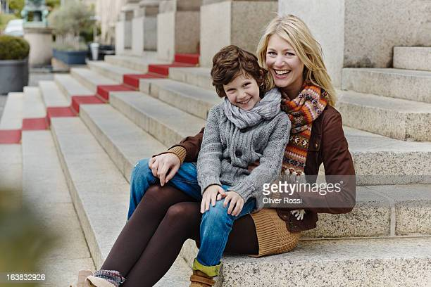 happy mother and son sitting on stairs - mom sits on sons lap stock pictures, royalty-free photos & images