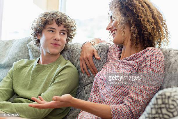 Happy mother and son talking on couch in living room