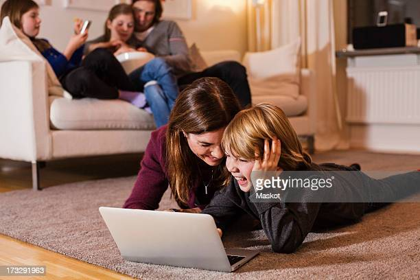 Happy mother and son using laptop on floor with family sitting on sofa in living room