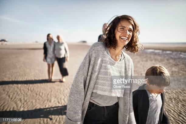 happy mother and son walking on the beach - mid adult women stock pictures, royalty-free photos & images