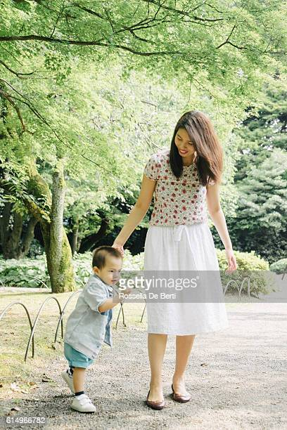 happy mother and son walking together outdoors in a park - female wrestling holds stockfoto's en -beelden