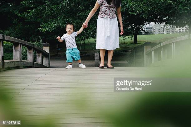 happy mother and son walking together outdoors in a park - kin in de hand stock pictures, royalty-free photos & images
