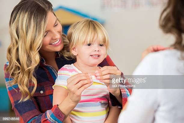 Happy mother and toddler daughter practicing sign language