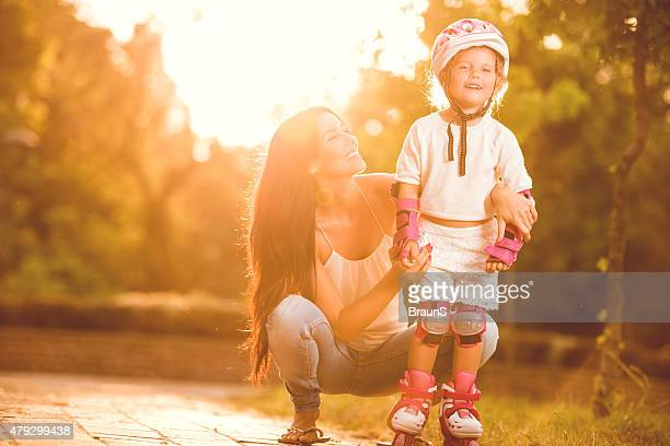Happy mother assisting her daughter in rollerblading at sunset.